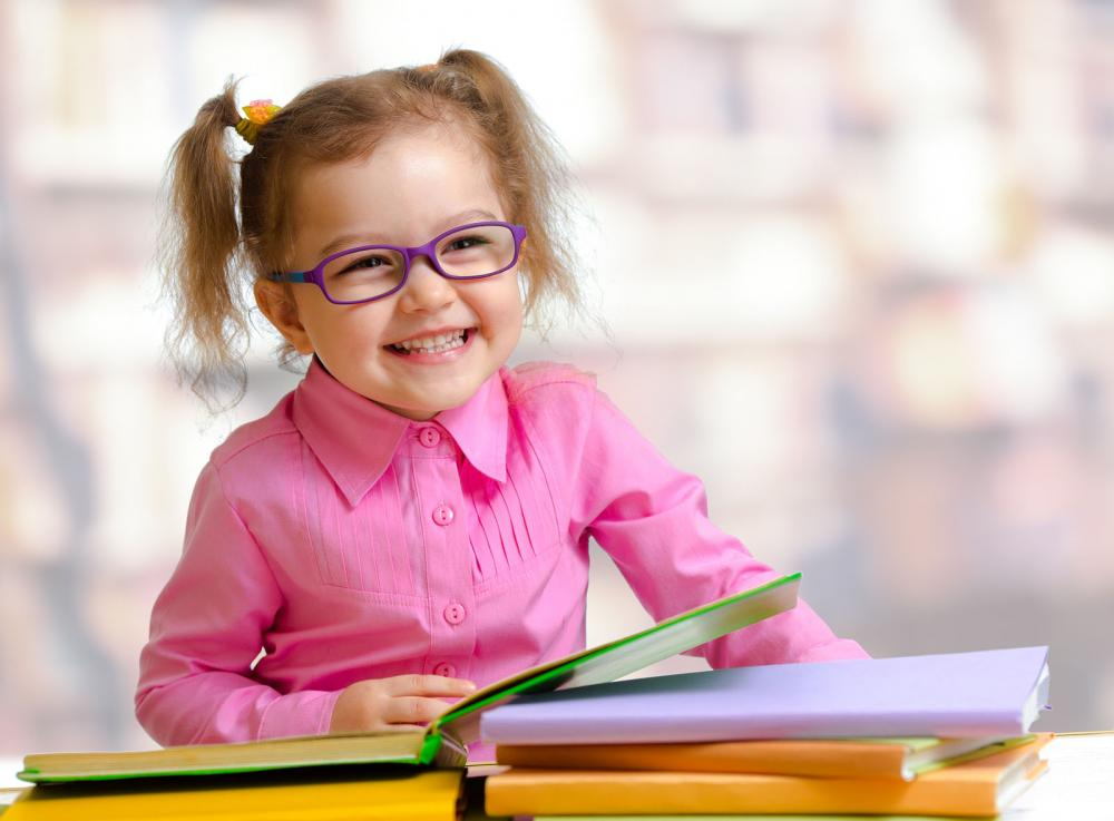 Little girl having fun reading with her new glasses.